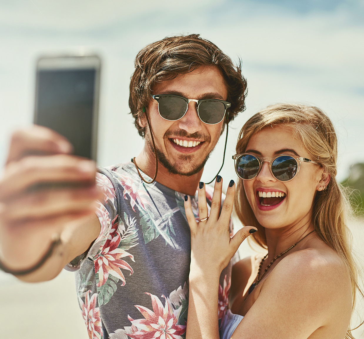 Cleveland couple engaged on the beach taking a selfie with ring purchased at Todd's Jewelers